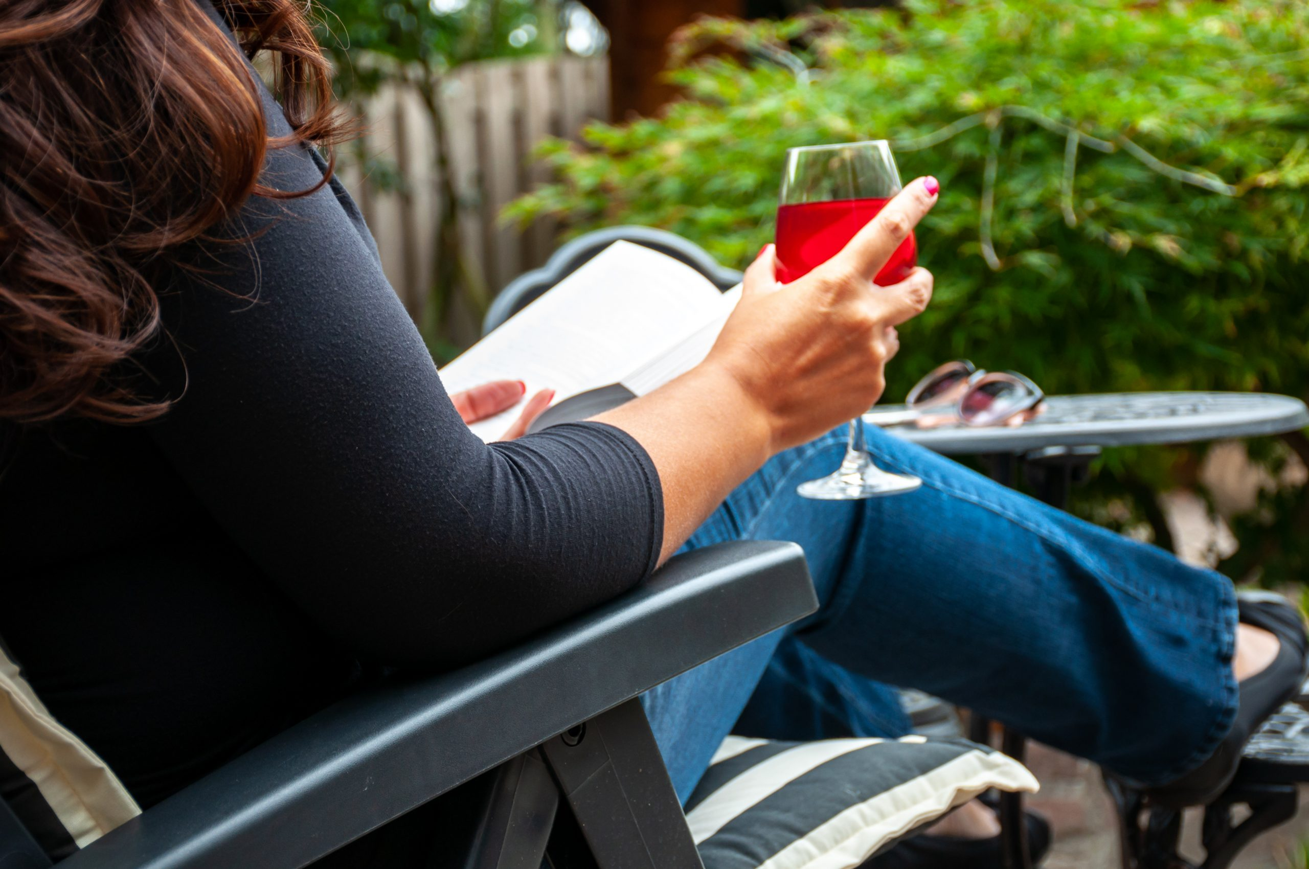 woman in black shirt and blue jeans drinking glass of red wine outside