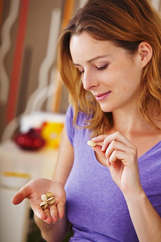 Woman eating pistachios